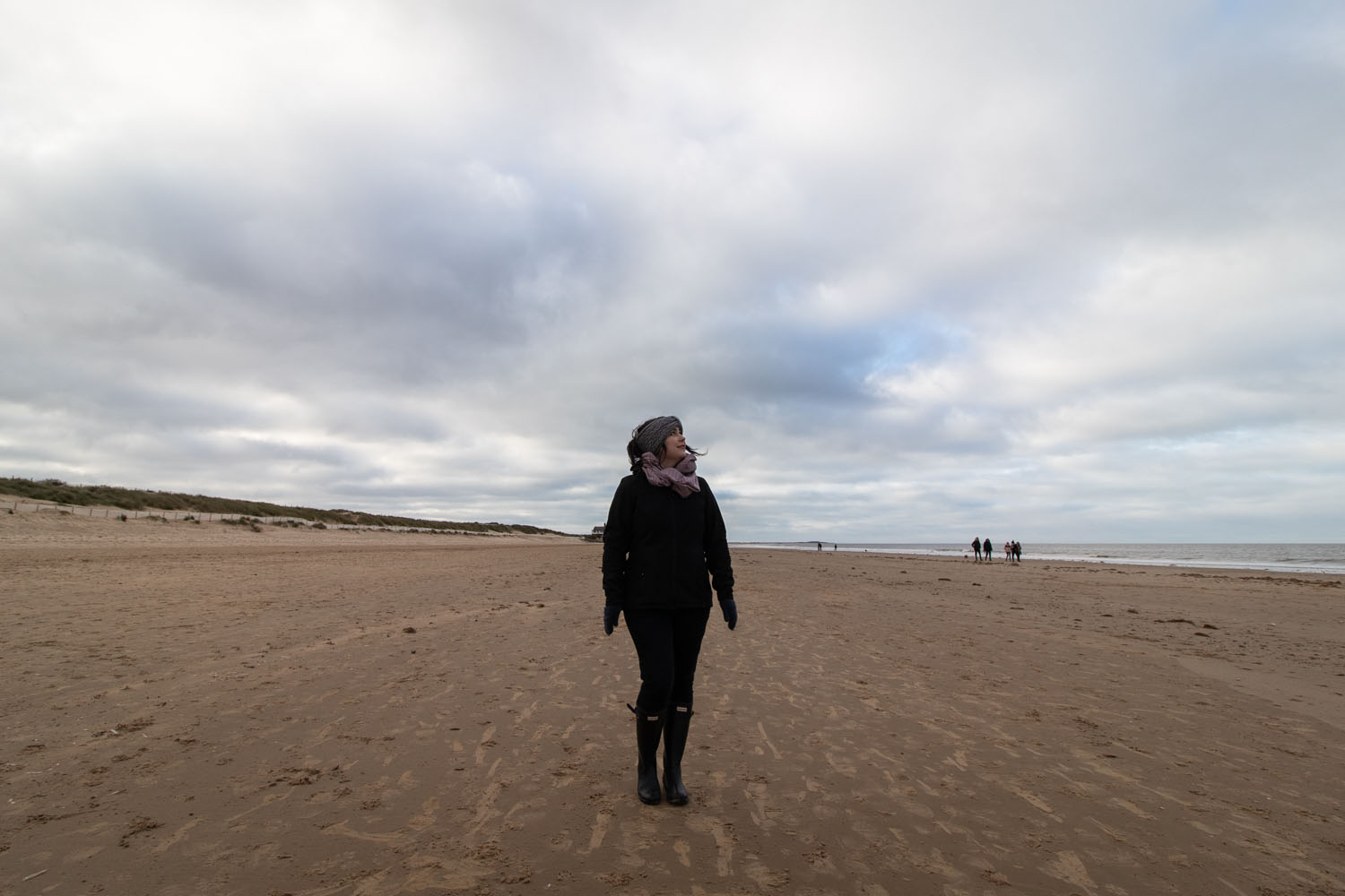 woman stood on beach looking out to sea