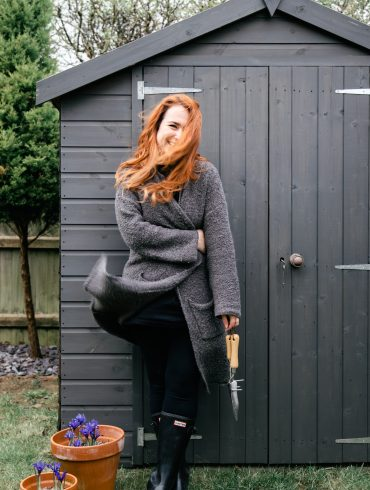 Woman stood in front of grey shed with garden tools in hand and flower pots to the side