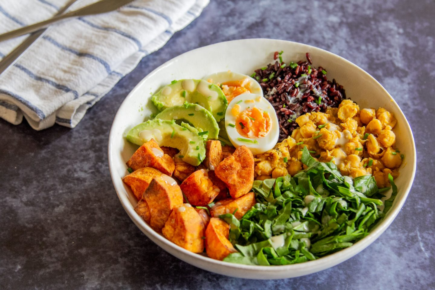 Bowl of rice, chickpeas, spinach, sweet potato, avocado and egg