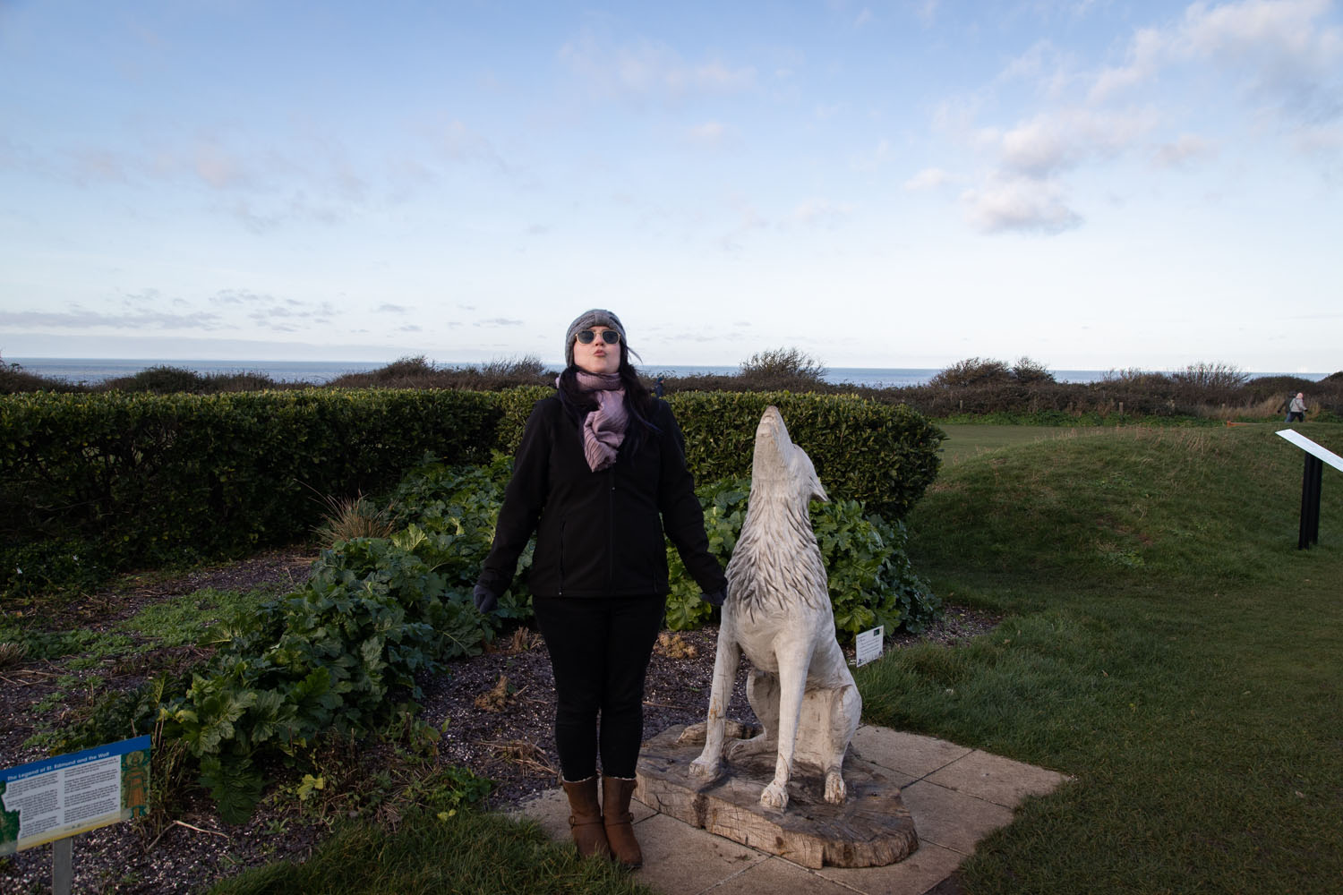 Woman howling next to statue of howling wolf