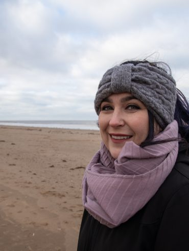woman on beach smiling wearing purple scrarf and grey headband