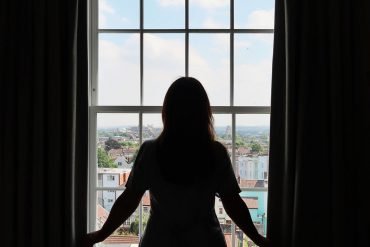 silhouette of woman stood by a window