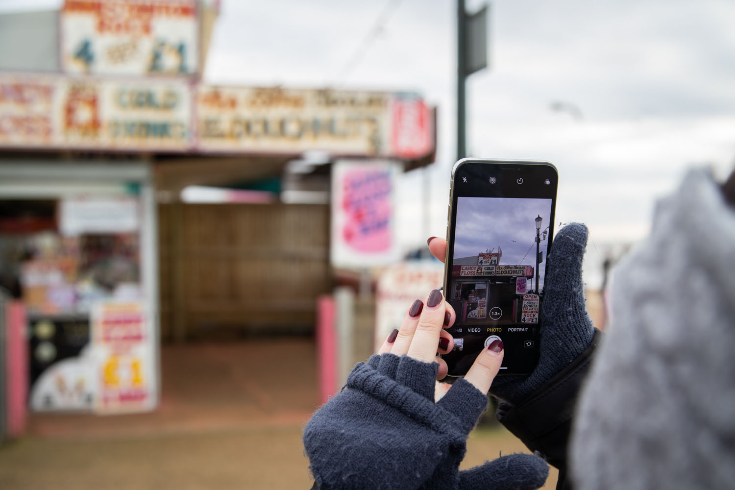 Woman holding phone taking picture of seaside snack shop