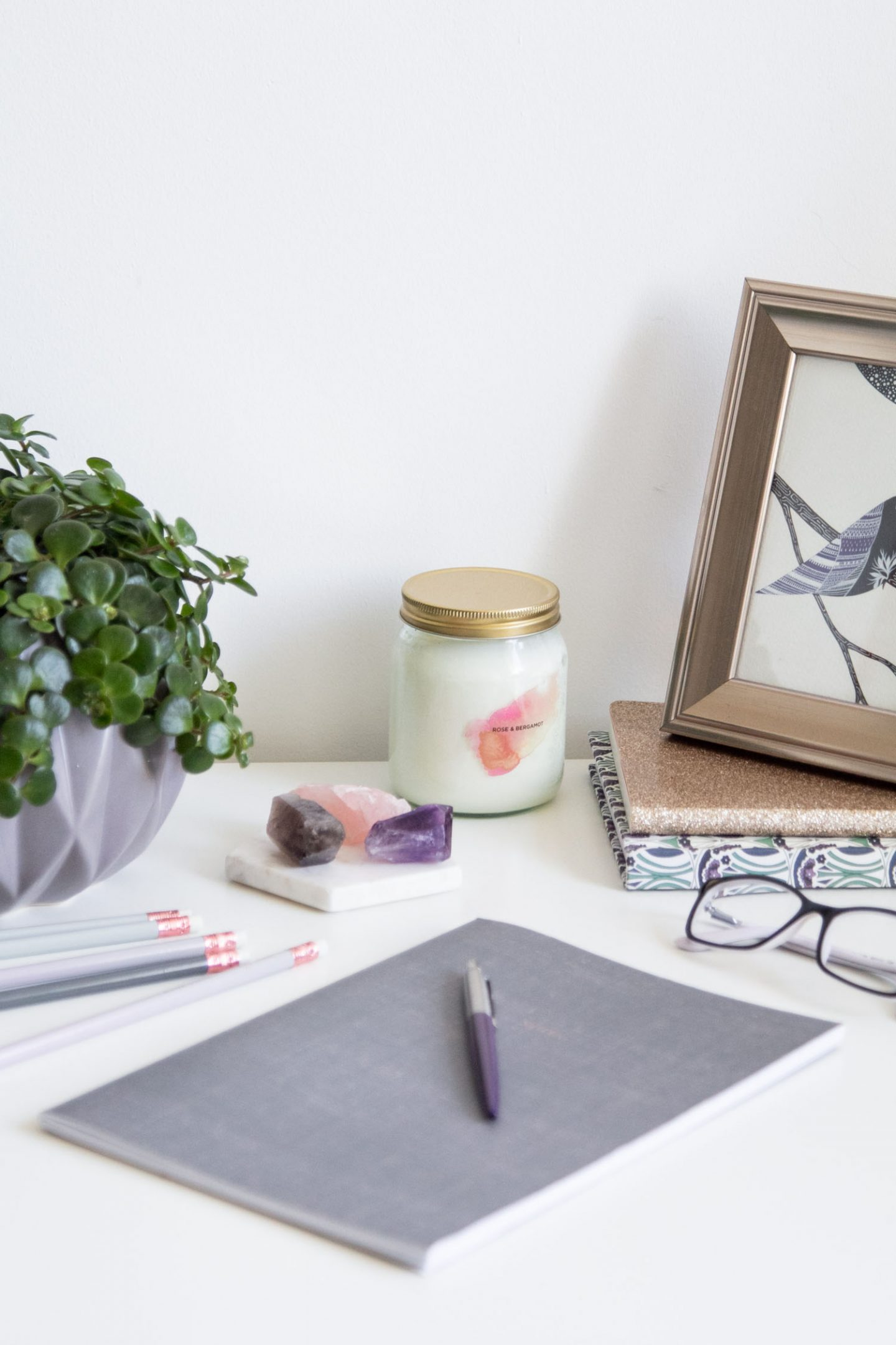 desk scene with notebook, plant, pen, candle, painting, glasses