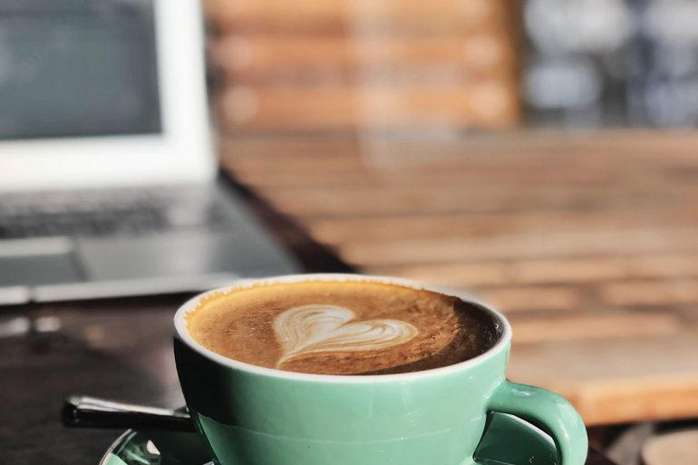 cup of coffee with laptop in background