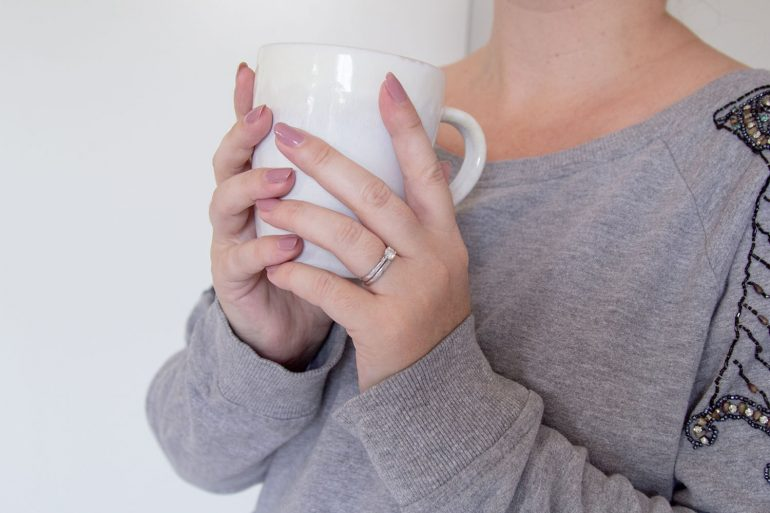 woman holding a cup of coffee in her hands
