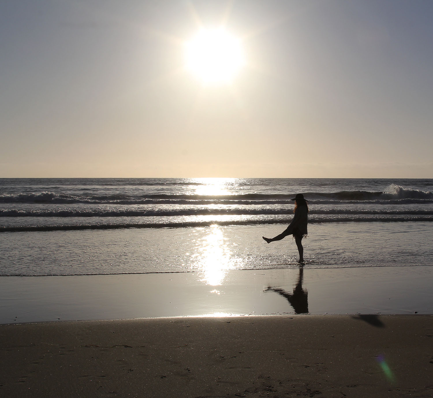 sunset at the beach with silhouette of woman kicking the water as the waves come in